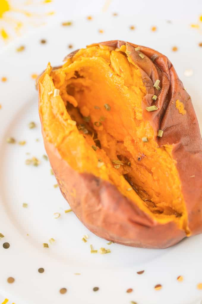 baked whole sweet potato on a white plate with polka dots