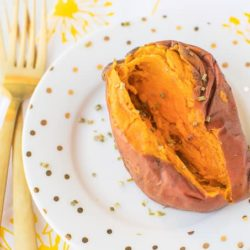 cooked sweet potato on a white plate with gold forks