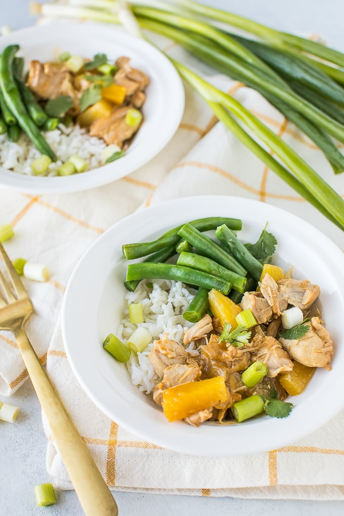 instant pot teriyaki chicken in two white bowls with green onions