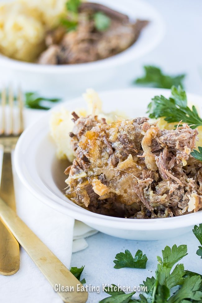 slow cooker corned beef and cabbage in white bowls with parsley