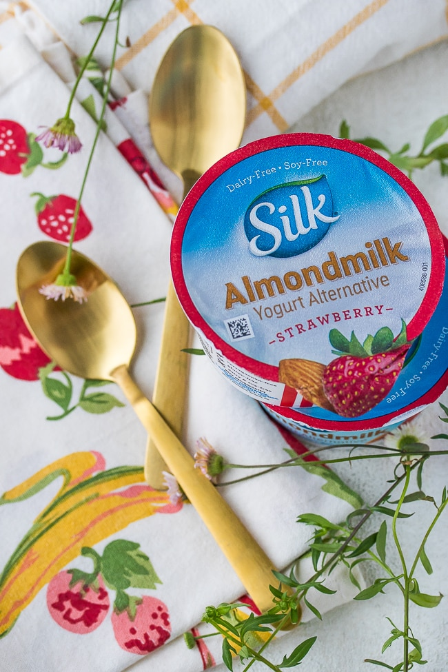 silk almond milk yogurt alternative in strawberry with gold spoons and flowers