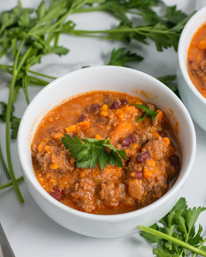instant pot beef sweet potato chili in a white bowl with parsley