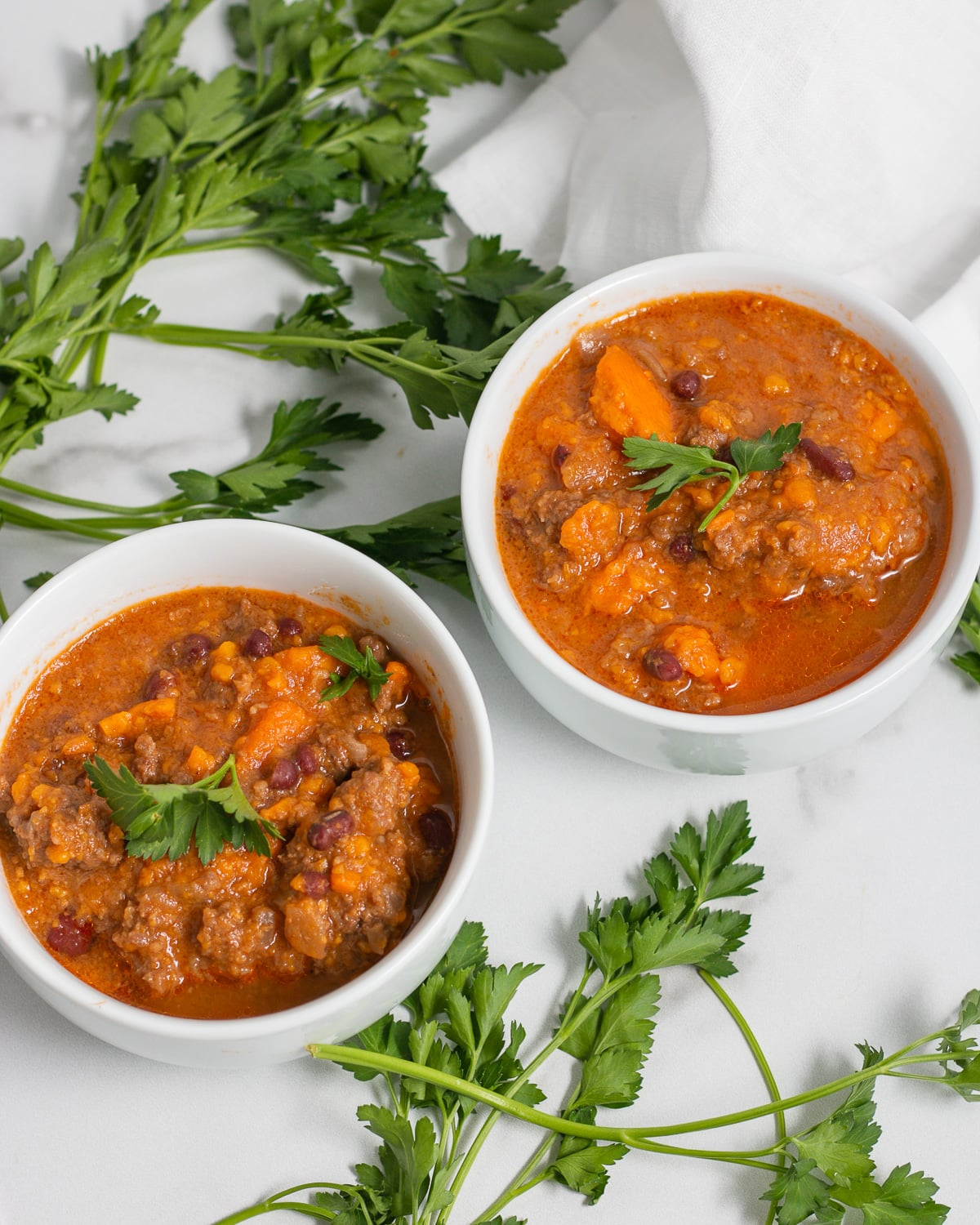 two bowls of chili with parsley on top
