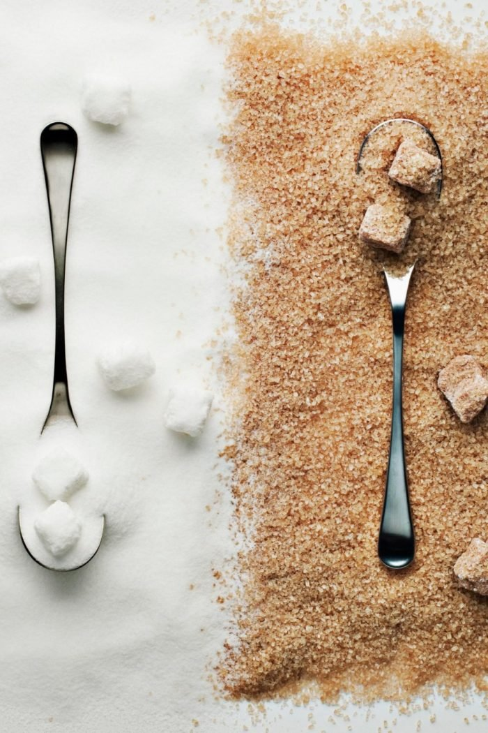 two spoons on a counter with white sugar and brown sugar