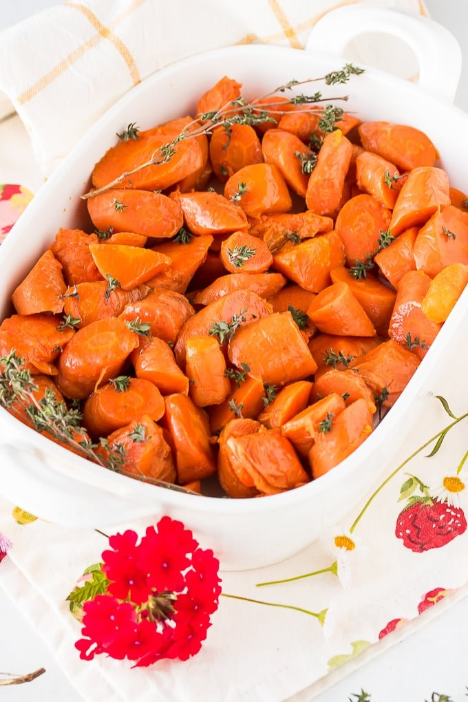 cooked carrots in a white baking dish