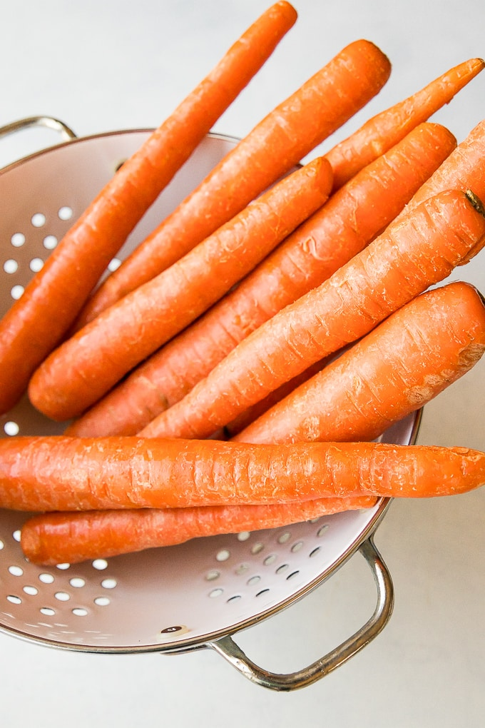 long unpeeled carrots in a white colander