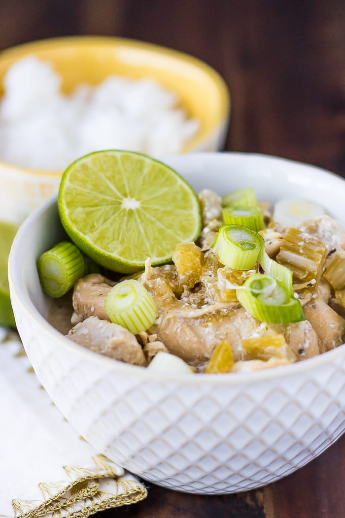instant pot coconut chicken in a white bowl with green onions