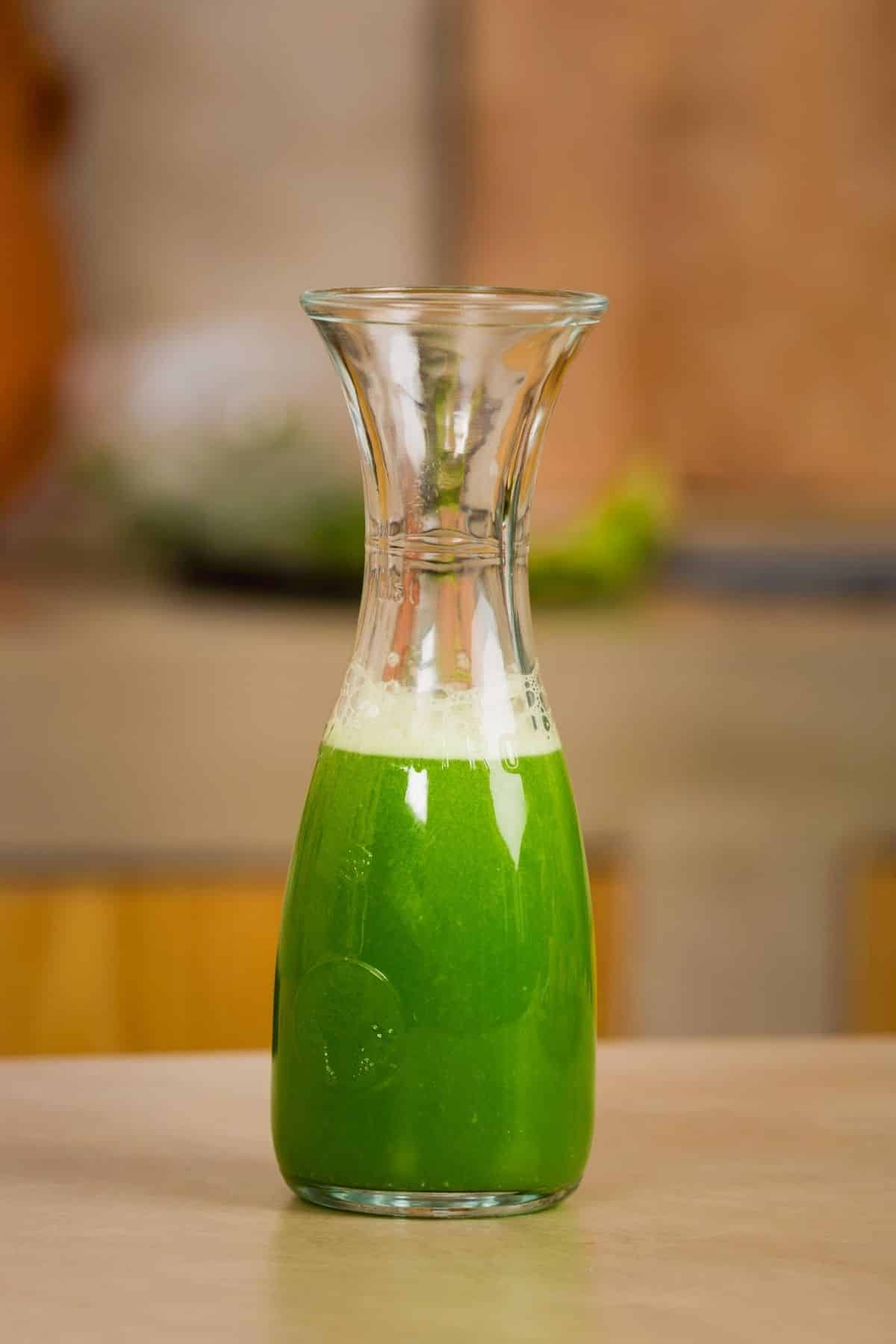 carafe of green juice on a table