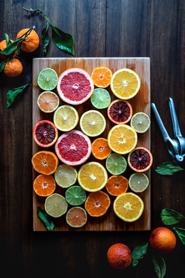 sliced citrus fruits on a wooden cutting board