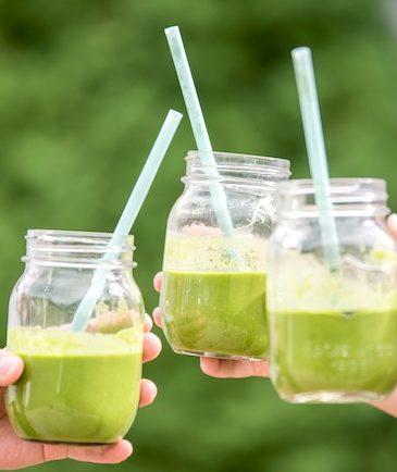 three jars of green juice with three hands