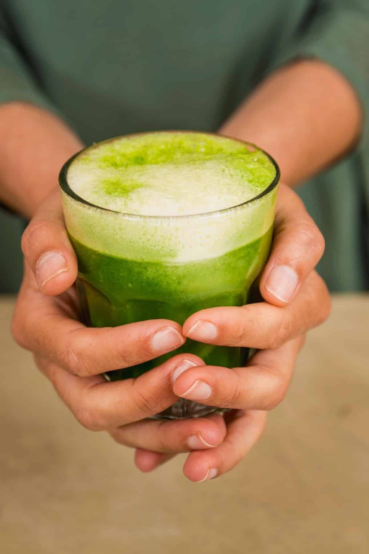 two hands holding a glass of green juice with foam on top