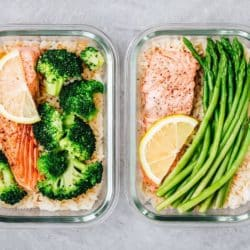 two meal prep bowls with salmon and veggies