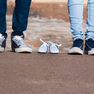 Baby Shoes with parents standing on either side