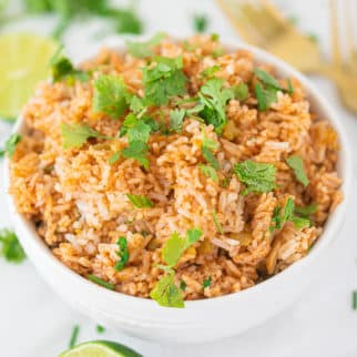 spanish rice in a bowl with two gold forks