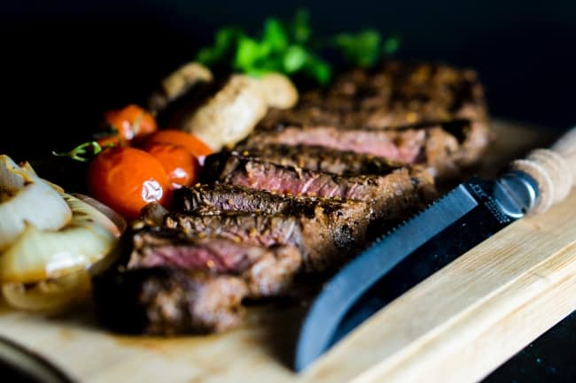 Grilled vegetables and steak on a wooden board