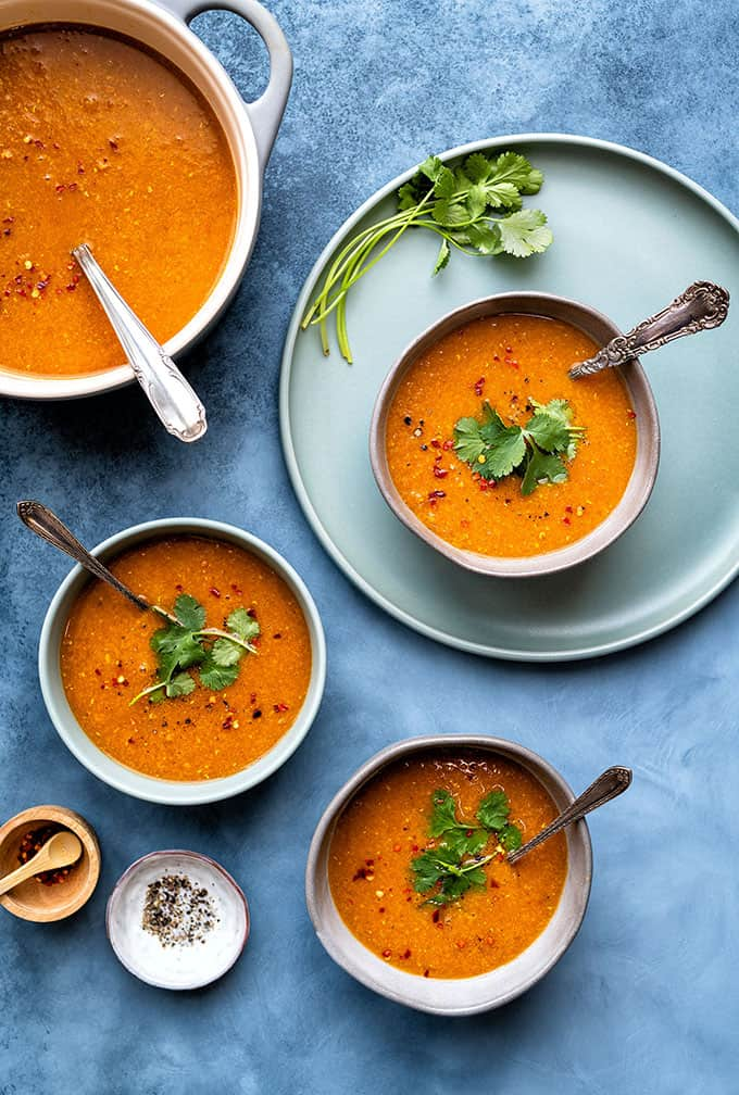 Red lentil soup served in bowls on a blue background