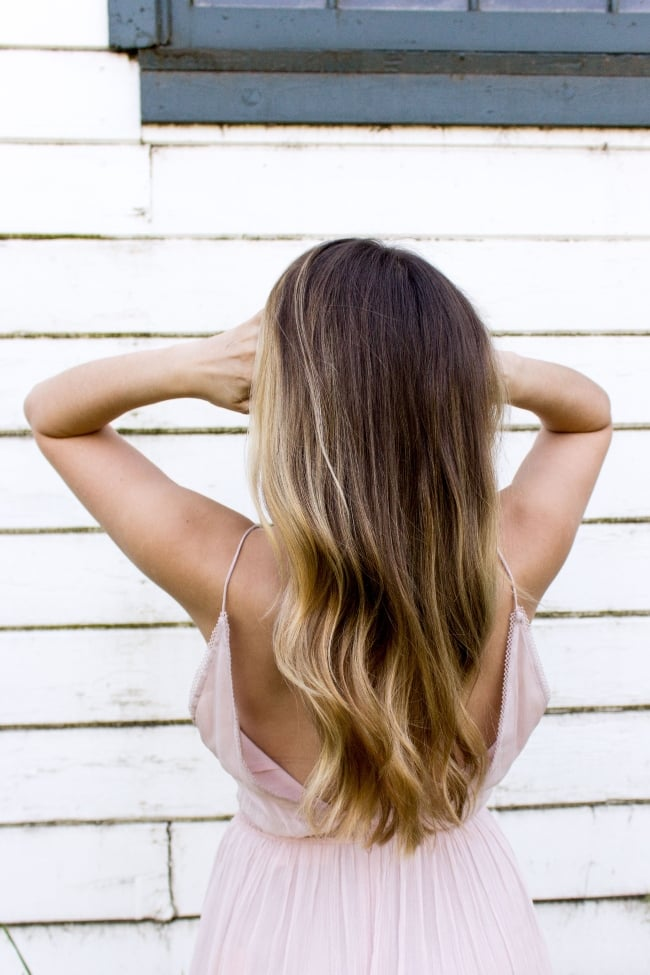 woman with shiny hair standing near a wall