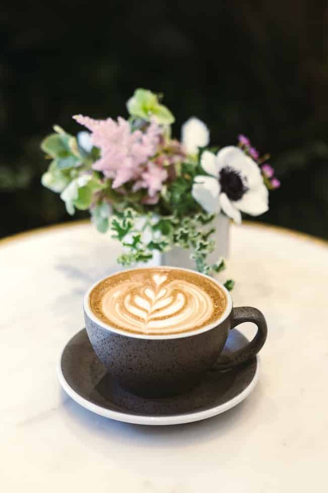 oat milk latte with flowers in background