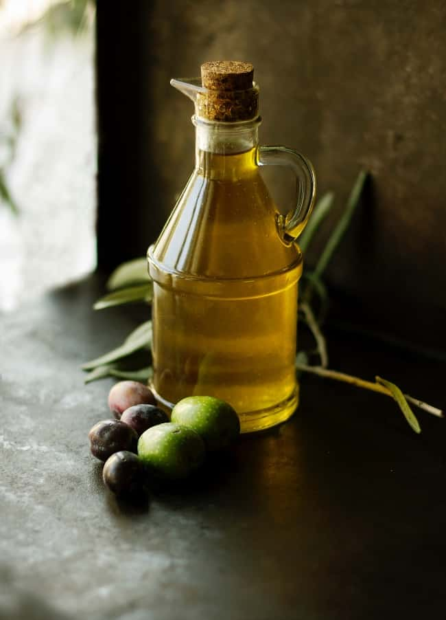 olive oil next to fresh olives