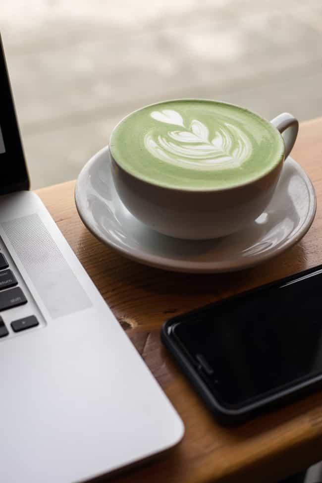 Matcha latte beside a computer