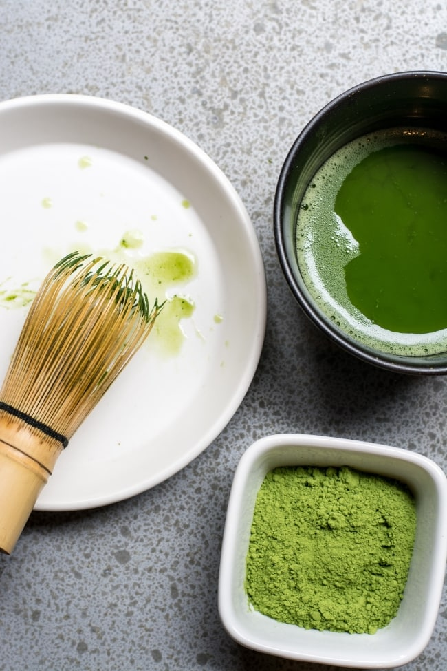 Matcha ingredients on a table with Matcha whisk