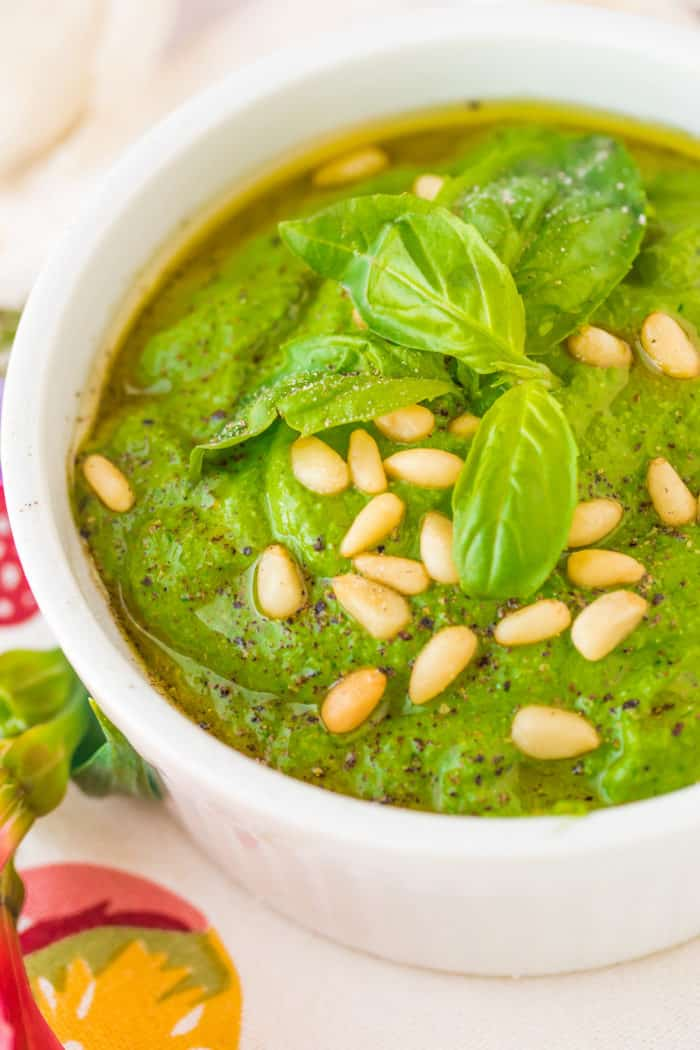 pesto sauce in a white bowl with fresh basil on top