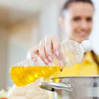 woman pouring oil into a pot
