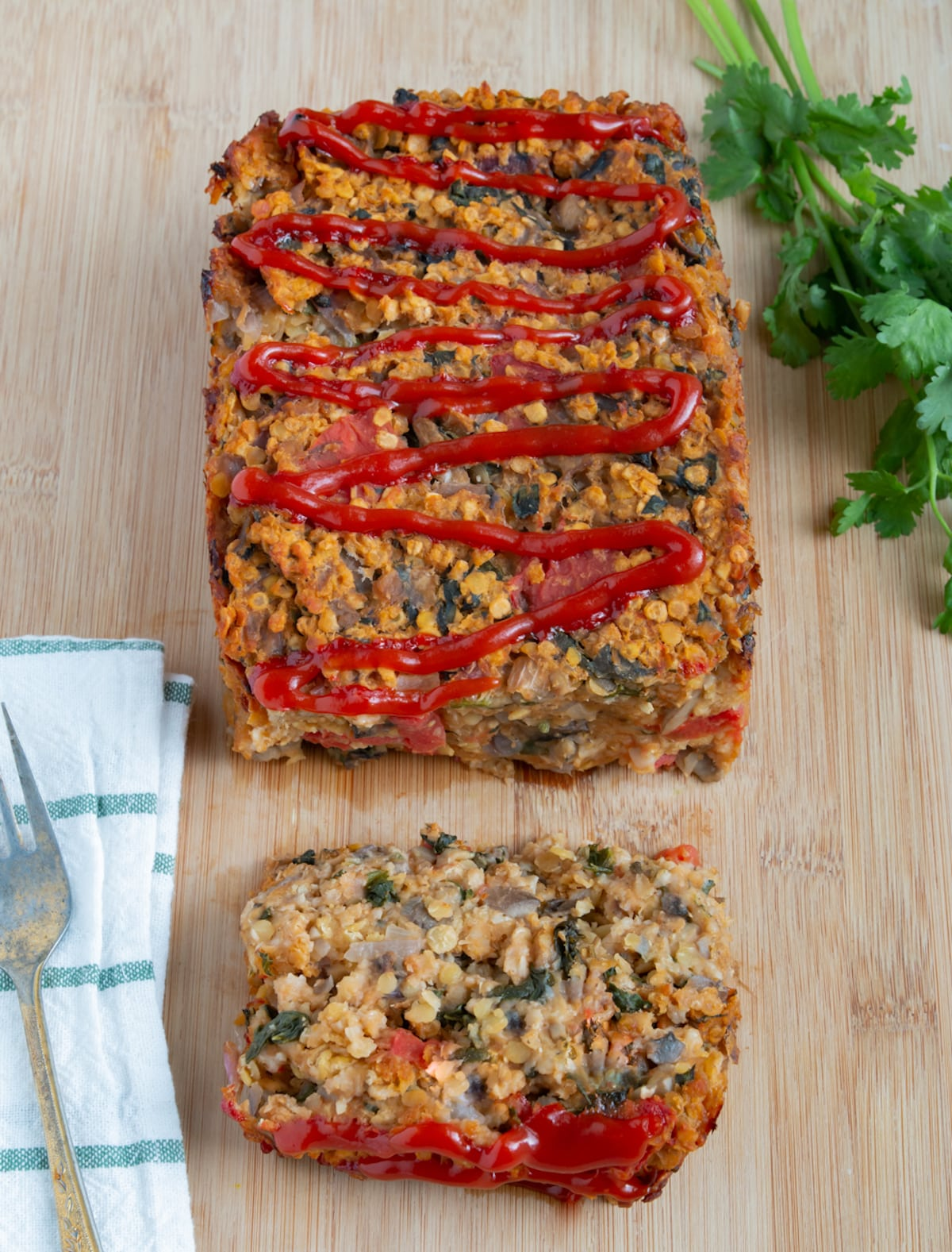 sliced vegan lentil loaf with a ketchup drizzle on top