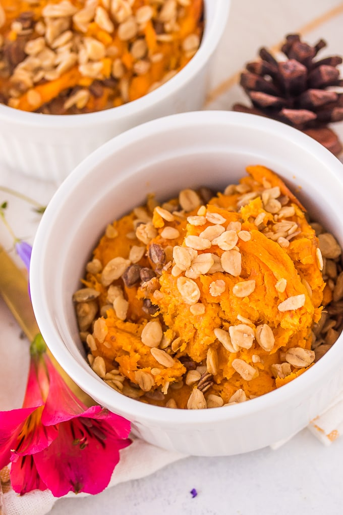 up close bowl of sweet potato casserole with granola topping and pine cones in the background