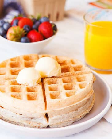 vegan waffles on a plate wit orange juice and berries