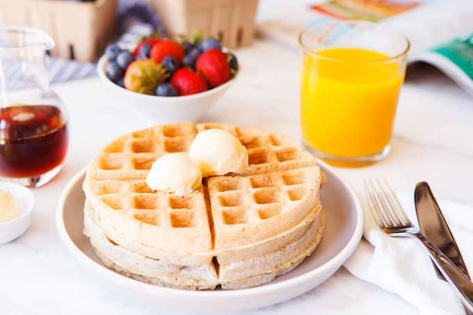 Breakfast setting with waffles, orange juice, berries, and maple syrup.