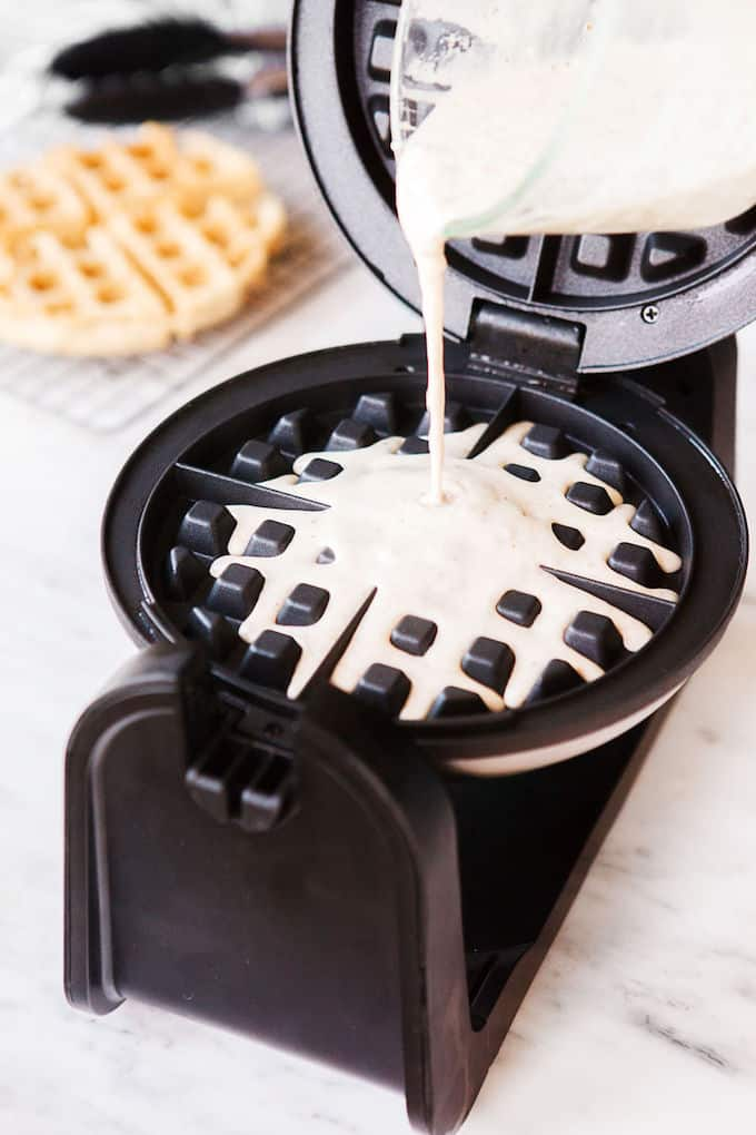 Batter being poured onto waffle maker.
