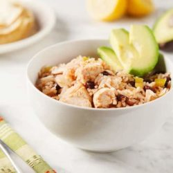 crockpot chicken and rice with sliced avocado in a white bowl