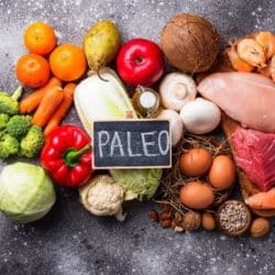 fruits and vegetables and meats on a countertop with a sign that says paleo
