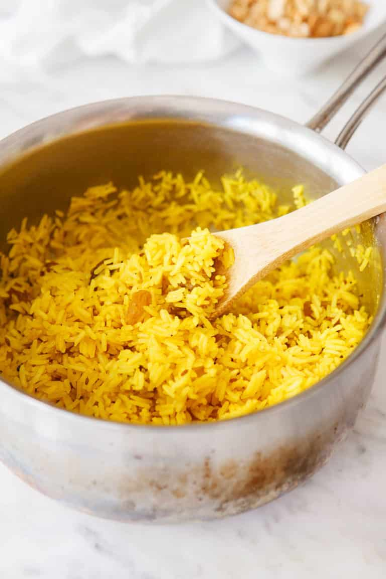 Fluff the yellow rice in the saucepan.