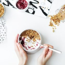 Bowl of granola with a woman's hand holding a spoon