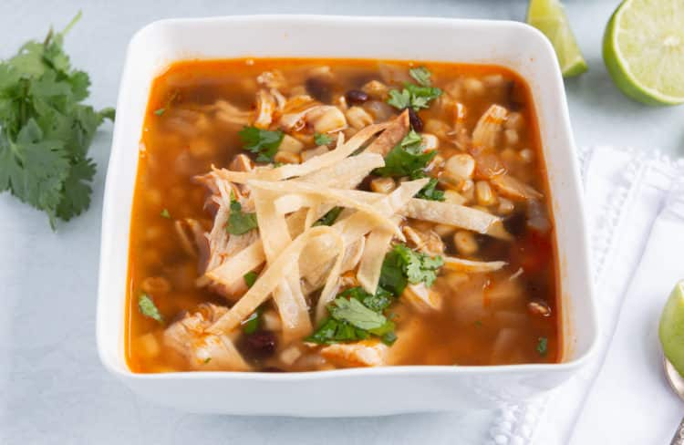 Easy chicken tortilla soup made in the instant pot and topped with crunchy tortilla strips.