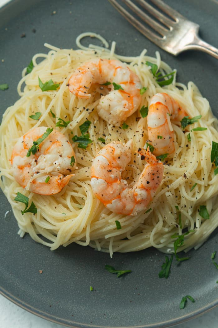 Shrimp and angel hair pasta on a plate.