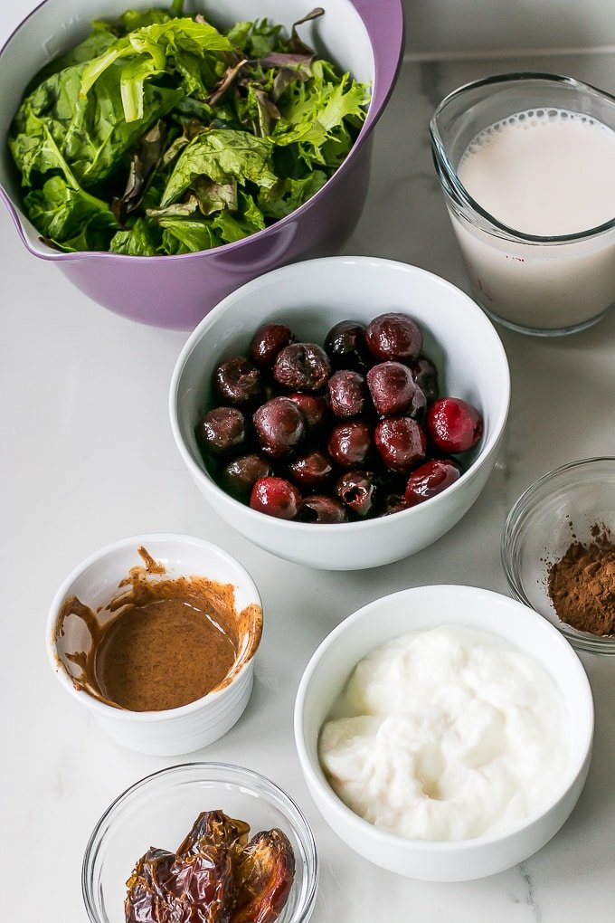 Ingredients for a healthy breakfast smoothy loaded with fruit and greens.