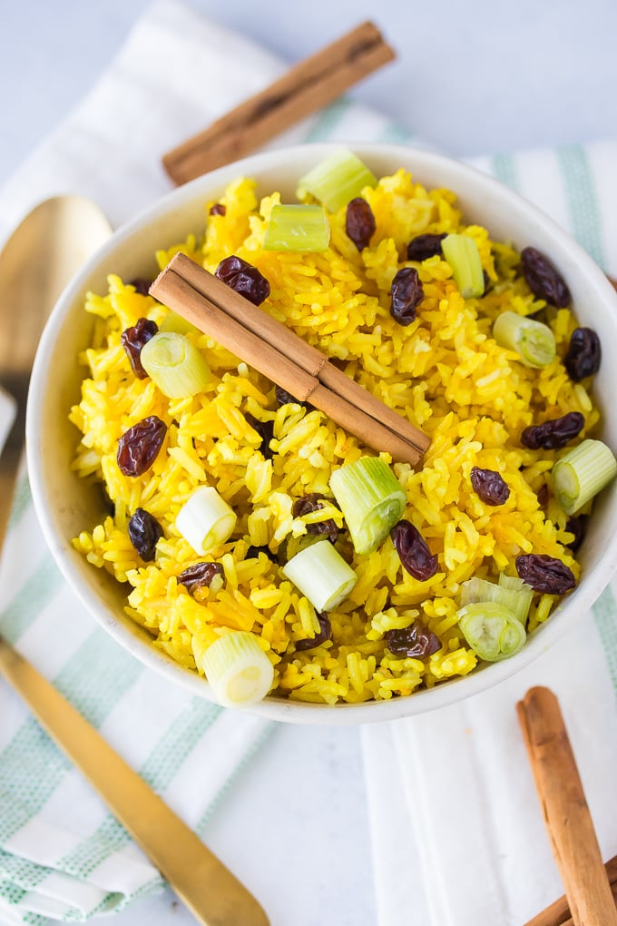Rice with raisins and green onions in a bowl.