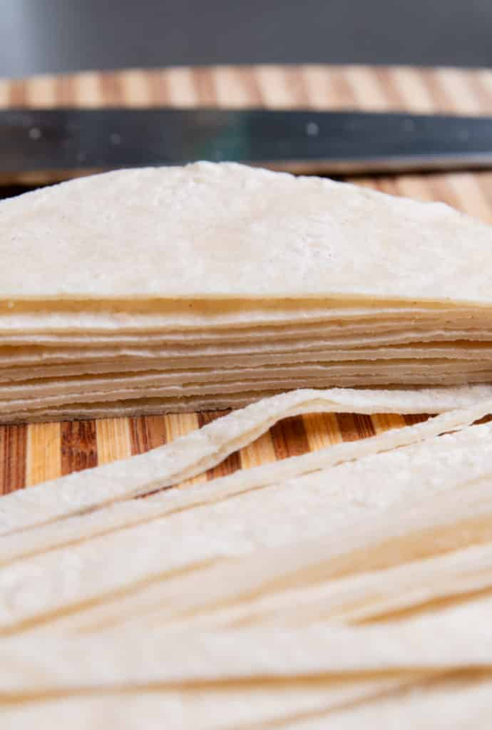Stacked tortillas sliced and ready to be baked into crunchy strips.