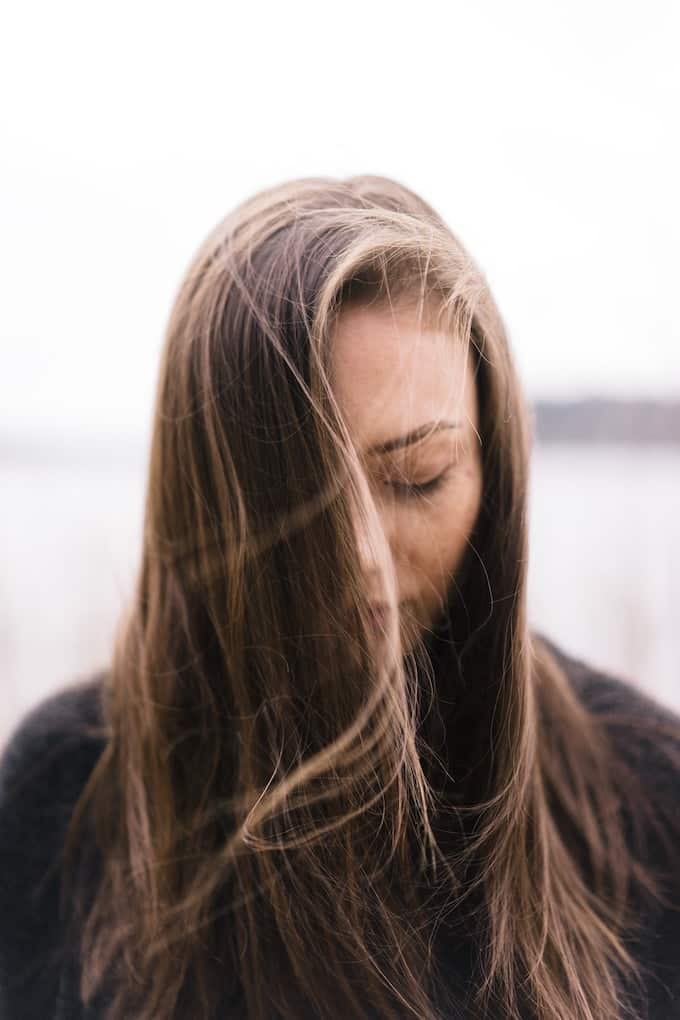 anxious woman with long hair looking downward