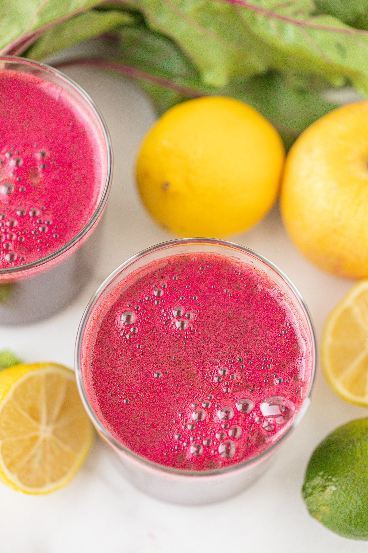 two glasses of fresh beetroot juice on a countertop with fresh lemons