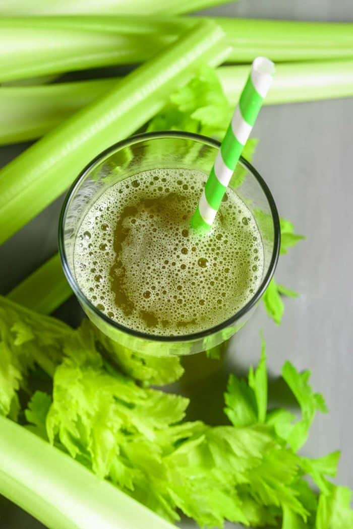 celery juice in glass with green striped straw