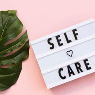 sign that says self care on it next to a plant