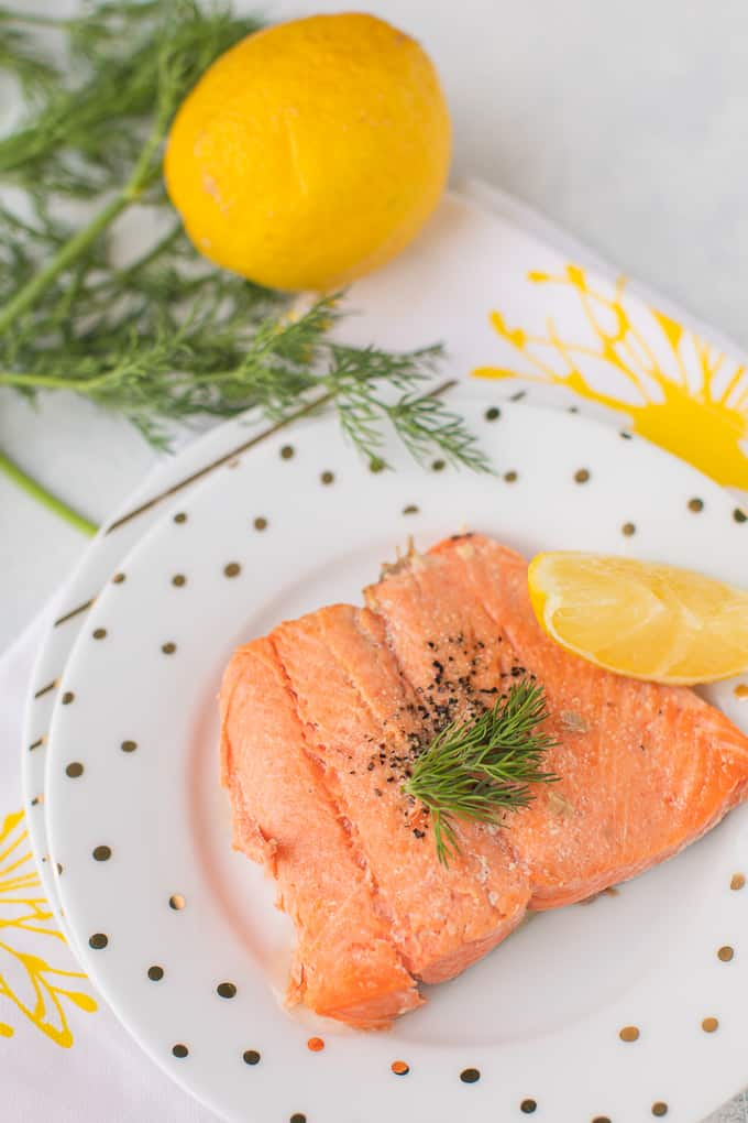 cooked salmon on a white plate with lemon and fresh dill