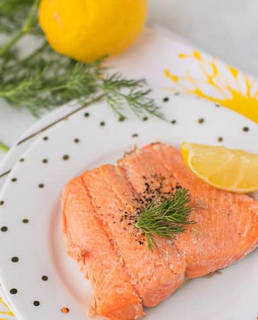 cooked salmon with lemon and dill on a plate