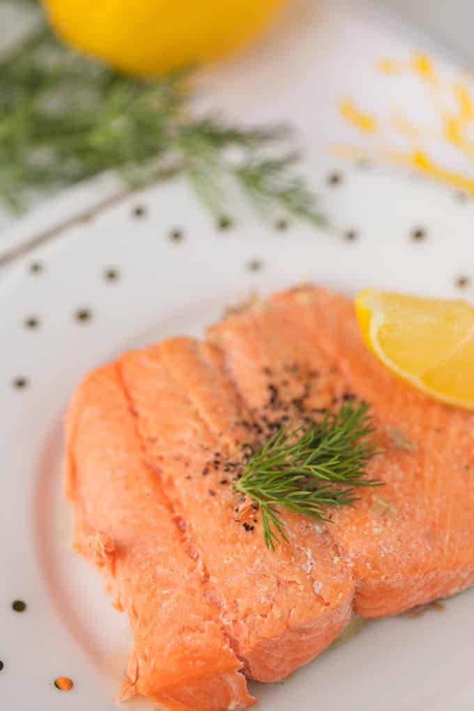 air fryer salmon on a plate with dill and lemon