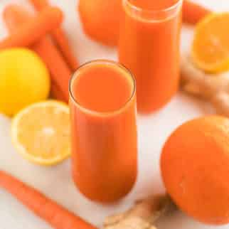 fresh carrot juice served in two glasses with orange, ginger, and lemon