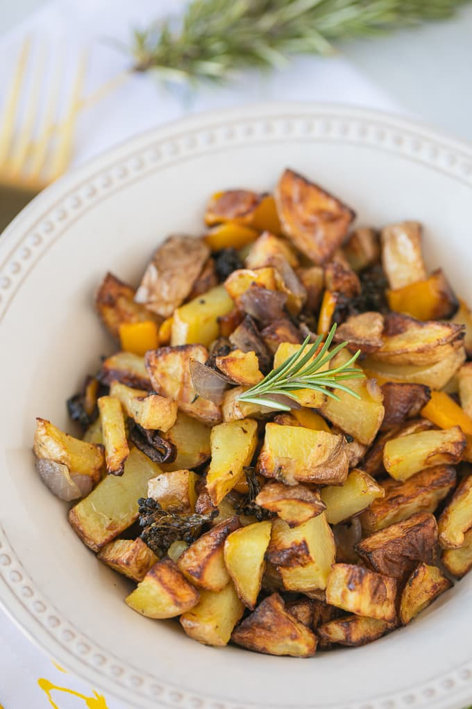 potatoes in a white bowl with a sprig of fresh rosemary on top
